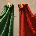 Red and green fabric hanging on clothesline in Lisbon, Portugal.