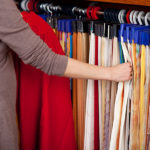 Woman choosing coloured fabric samples from a multitude of colours hanging on rails in an interior decorator