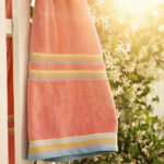 Sun flare through flowering vine with towel hanging on white picket fence.