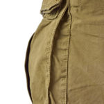 Military olive green army style cotton twill cargo pants storage pocket isolated macro closeup, large detailed camouflage trousers studio shot